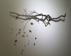 The Remnants, Burned sage brush branch, lake Michigan stones, gold leaf and thread, 2016